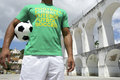 Brazilian football player holding soccer ball rio lapa wearing international shirt at arches in de janeiro Stock Images