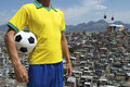 Brazilian football player soccer ball favela slum standing in brazil team colors kit uniform holding in front of background in rio Royalty Free Stock Images