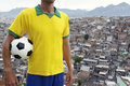 Brazilian football player soccer ball favela slum standing in uniform holding in front of background in rio de janeiro Royalty Free Stock Images