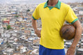 Brazilian football player vintage soccer ball favela stands in brazil team colors holding in front of background in rio de janeiro Royalty Free Stock Photography