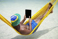 Brazilian man relaxes using tablet in hammock on beach uses computer relaxing over the sea Royalty Free Stock Images