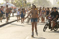 Brazilian recreating rio de janeiro brazil january man on electric bike follows woman on inline skates and crowds of people on Stock Images