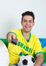 Brazilian soccer fan watching football live on television laughing with ball and flag Royalty Free Stock Photo