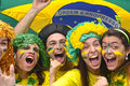 Brazilian soccer fans commemorating group of happy victory with flag in the background Stock Photos