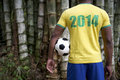 Brazilian soccer football player jungle bamboo in shirt standing in front of tropical background holding Stock Photo