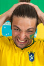 Brazilian sports fan in dispair despairing watching his national team fail an important game Stock Photos