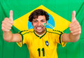 Brazilian sports fan supporting his national team cheering with his outstreched arms and thumbs up in front of a brazil flag Stock Photography