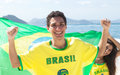 Brazilian sports fans with jersey and flag Royalty Free Stock Photo