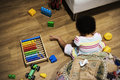 Brazilian toddler girl playing wooden toys on the floor Royalty Free Stock Photo