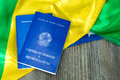 Brazilian work document and social security document on the table (Carteira de Trabalho) on brazilian flag Royalty Free Stock Photo