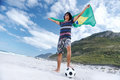 Brazillian soccer man latino brasil football fan with flag and ball on beach Royalty Free Stock Photos