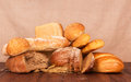 Bread abundance and ears of wheat on wooden table Stock Photo