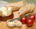 Bread and butter delicious organic home made bread and butter with ripe tomatoes on wooden board Stock Photo