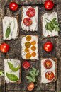 Bread with cheese tomatoes with herbs on a cutting board on wooden rustic background top view Royalty Free Stock Photo