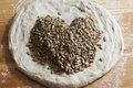 Bread dough with seeds forming a heart Royalty Free Stock Photo