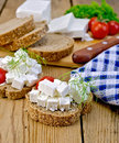 Bread with feta and tomatoes on board with knife slices of cheese tomato dill napkin wooden Royalty Free Stock Image