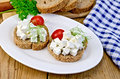 Bread with feta and tomatoes on plate on board slices of cheese tomato dill a napkin the background of wooden boards Stock Photo