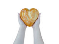 Bread in the form of heart on oak in female hands isolated on white background Royalty Free Stock Photo