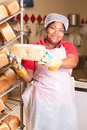 Bread hot and fresh young african woman wearing heat protected gloves preparing loaves to be cooled on the rack Royalty Free Stock Images