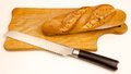 Bread with a knife on a cutting board, on white background Royalty Free Stock Photo