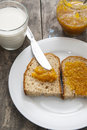 Bread with orange jam and glass of milk on wooden table close up photo Stock Photos