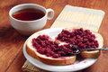 Bread with raspberry jam and cup of tea on brown table Stock Images