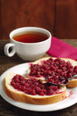 Bread with raspberry jam and cup of tea on table Stock Images