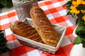 Bread on red and white table breakfast with flowers a picture of two fresh breads a Royalty Free Stock Photography