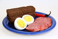 Bread, sausage, eggs and red peppers on blue plate Royalty Free Stock Image