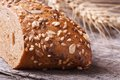 Bread with seeds and nuts closeup on wooden table background ears of wheat macro Stock Photo