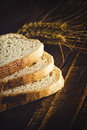 Bread slices wheat ears and grains with on wood table Royalty Free Stock Photo