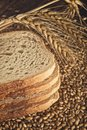 Bread slices wheat ears and grains with on wood table Stock Photo
