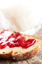 Bread with strawberry jam and glass of milk angled on wooden table Royalty Free Stock Image