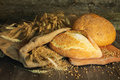Bread, wheat, ears of corn on a wooden background Royalty Free Stock Photo
