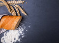 Bread, wheat ears and flour on the black background Royalty Free Stock Photo