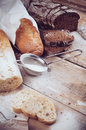 Bread white french baguette and fresh rustic loaf of wholemeal rye sliced ​​and flour on a wooden board bakers food background Stock Photos