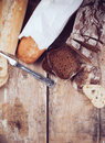 Bread white french baguette and fresh rustic loaf of wholemeal rye sliced ​​and flour on a wooden board bakers food background Royalty Free Stock Images