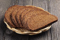 Bread in a wicker plate on vintage wooden table closeup Stock Photos