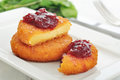 Breaded and baked camembert with cranberry sauce on white plate closeup Royalty Free Stock Image