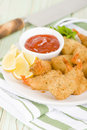 Breaded butterfly prawns deep fried battered filled with garlic sauce served with chili sauce and lemon wedges Royalty Free Stock Photo