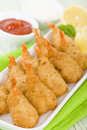 Breaded butterfly prawns deep fried battered filled with garlic sauce served with chili sauce and lemon wedges Royalty Free Stock Photography