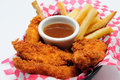 Breaded chicken strips with french fries and dipping sauce in a diner basket Royalty Free Stock Images