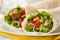 Breaded chicken in a tortilla wrap with lettuce and tomato Stock Photos