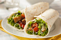Breaded chicken in a tortilla wrap with lettuce and tomato Royalty Free Stock Photos