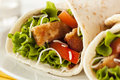 Breaded chicken in a tortilla wrap with lettuce and tomato Royalty Free Stock Image