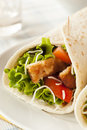 Breaded chicken in a tortilla wrap with lettuce and tomato Stock Images
