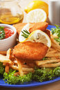 Breaded fish steaks with french fries Stock Photography