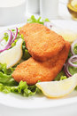 Breaded fish steaks with lemon and lettuce Stock Photo