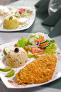 Breaded schnitzel served with rice and fresh salad selective focus Stock Photo