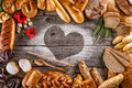 Breads, pastries, christmas cake on wooden background with heart, picture for bakery or shop, valentines day Royalty Free Stock Photo